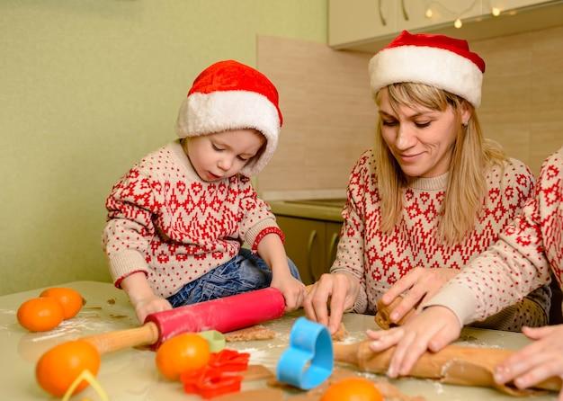 귀여운 아이들과 어머니는 크리스마스 쿠키를 굽습니다. 좋아하는 가족 전통. 행복한 가족. 웃기는 아이들이 반죽을 준비하고 부엌에서 진저 브레드 쿠키를 굽고 있습니다.