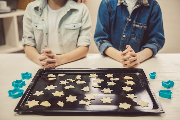 Cute children arranging cookies on baking sheet.