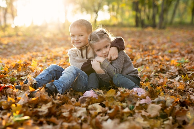 Cute children, boy and girl are playing, sitting and hugging together in autumn park.