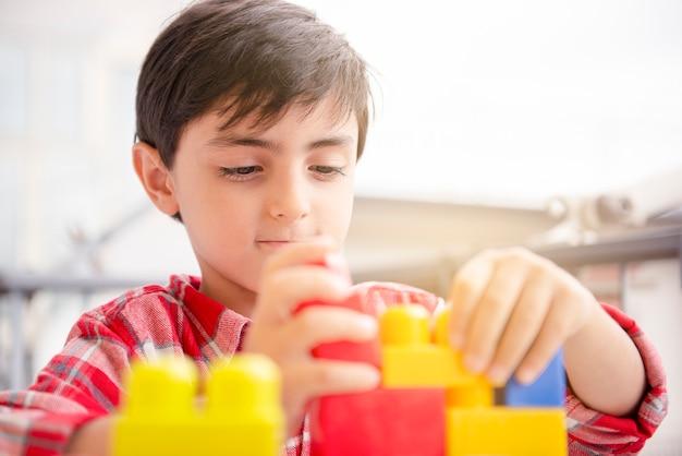 Cute children boy playing in terrace building blocks