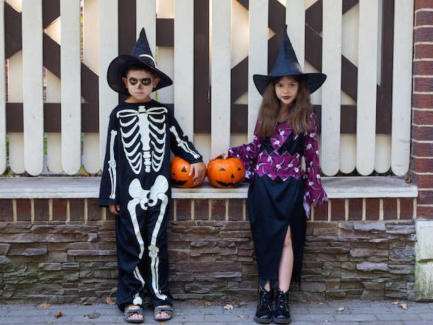 Cute children, a boy in a skeleton costume and a girl in a witch costume celebrate halloween