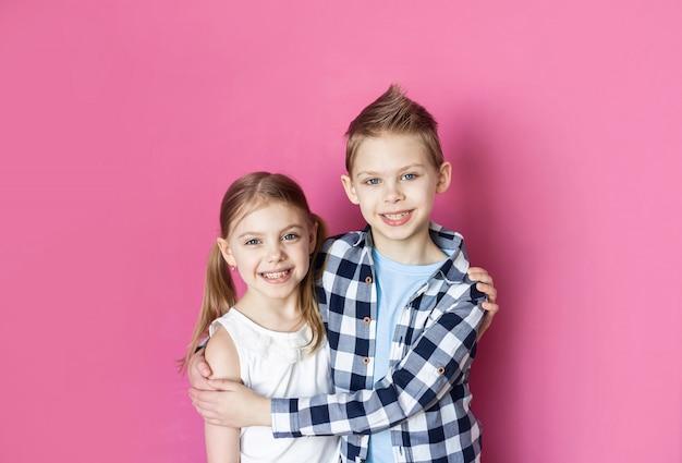 분홍색 벽에 귀여운 어린이, 형제 및 자매 7-9 세 미소