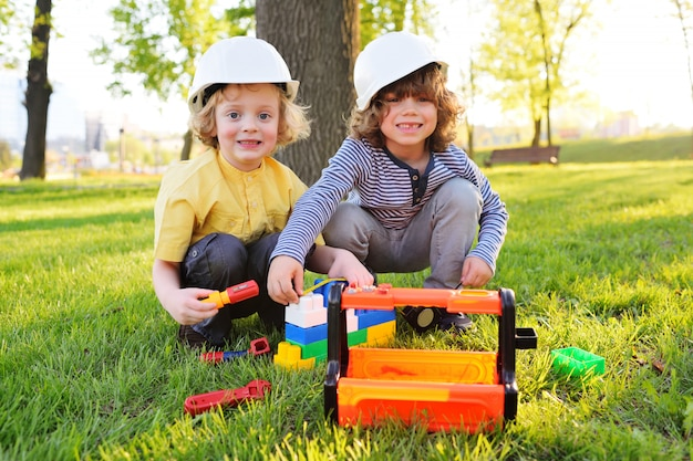Cute children in building helmets play in workers or builders with toy tools in a park on the grass.