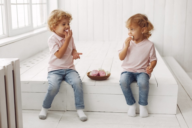 Cute children eating cookies at home