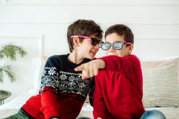 3d 안경으로 집에서 tv를 보면서 팝콘을 먹는 귀여운 아이들.
