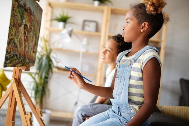かわいい子供たちの女の子と男の子が一緒に絵を描いています。教育、芸術、楽しさと創造性の概念。