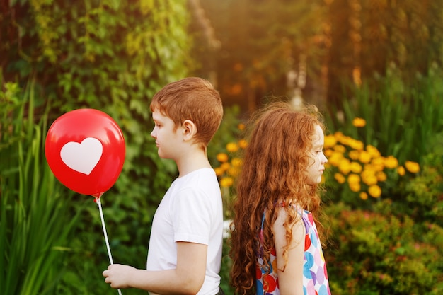 Cute children hold red balloons with heart  in summer park.