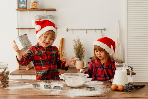 Cute children making cookies together on christmas day