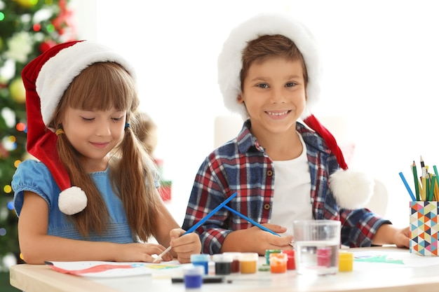 テーブルでクリスマスの絵を描くかわいい子供たち