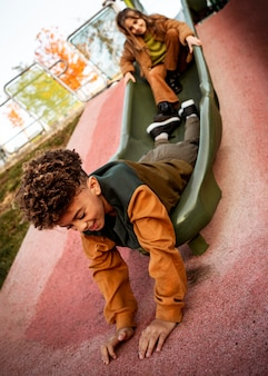 Cute children playing on a slide together