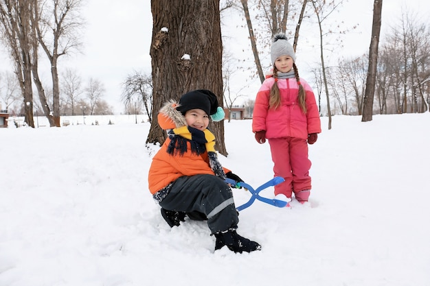 Cute children playing in snowy park on winter vacation