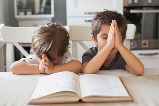 Cute children praying together at home