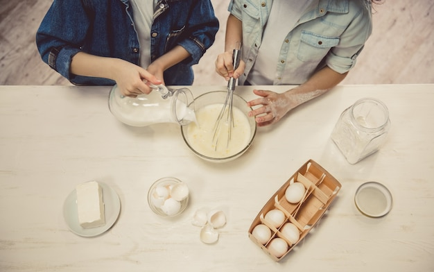 Cute children preparing dough while baking in the kitchen.