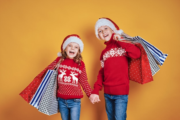 Cute children in red santa hats and sweaters hugging and holding shopping bags and golden balloons on yellow background