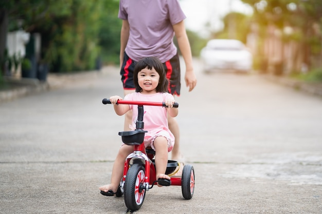 Cute children riding a bike with her mother. kids enjoying a bicycle ride.