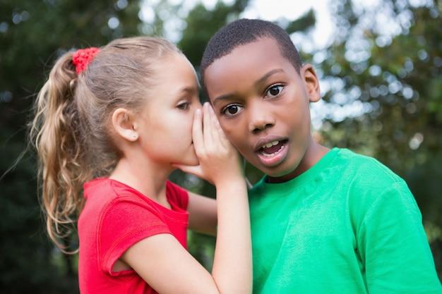 Cute children sharing gossip outside