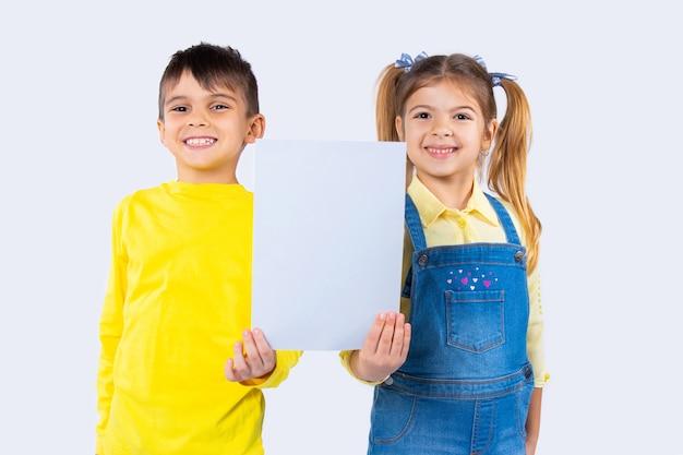 Симпатичные дети со счастливой улыбкой позируют с белым листом бумаги для вашей рекламы.