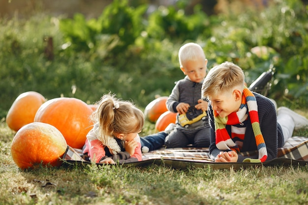 Cute childresn sitting on a garden near many pumpkins