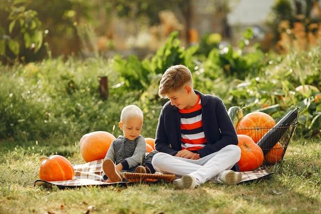 Cute childresn sitting on a garden near many pumpkins