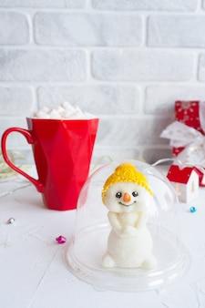 플라스틱 포장에 귀여운 초콜릿 눈사람 입상. 커피와 마쉬 멜 로우와 빨간색 선물 상자와 붉은 낯 짝.