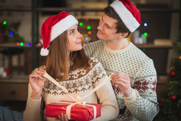 Cute christmas couple opening present