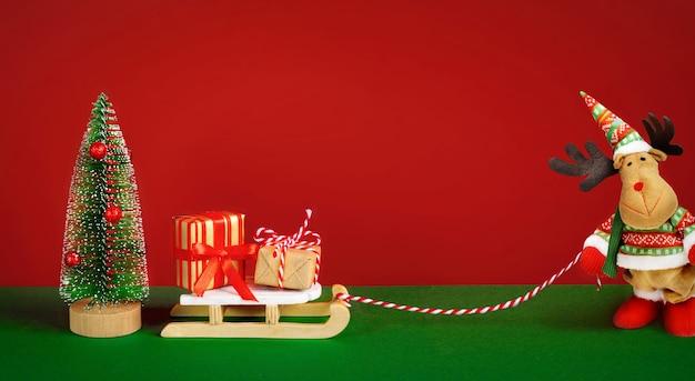 そりにギフトボックスと赤い背景に装飾的なクリスマスツリーとかわいいクリスマスのエルクまたはムース。