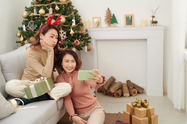 携帯電話の友達にプレゼントを見せてくれるかわいいクリスマスの女の子。