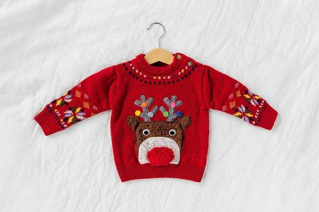 小さな赤ちゃんのための鹿とかわいいクリスマスセーター。クリスマスパーティー Premium写真