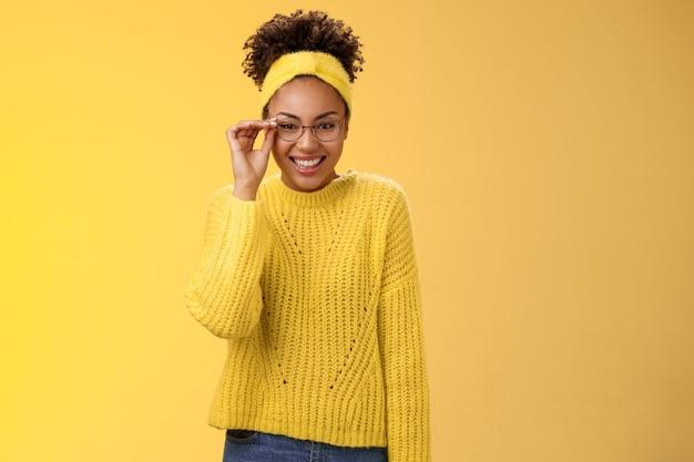 귀엽고 영리한 대학생 여대생 아프리카계 미국인 터치 안경 코가 활짝 웃으며 아르바이트 교사 어린이 영어 수업을 하며 친근한 노란색 배경 스웨터, 머리띠를 하고 있습니다.