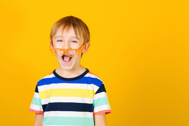 Cute clever boy in glasses on yellow