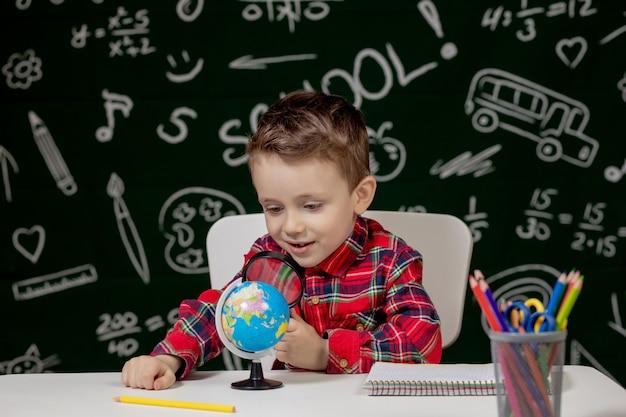 귀여운 영리한 소년 손에 돋보기와 책상에 앉아있다. 아이 배경에 칠판으로 책을 읽고 있습니다. 학교 갈 준비. 학교로 돌아가다