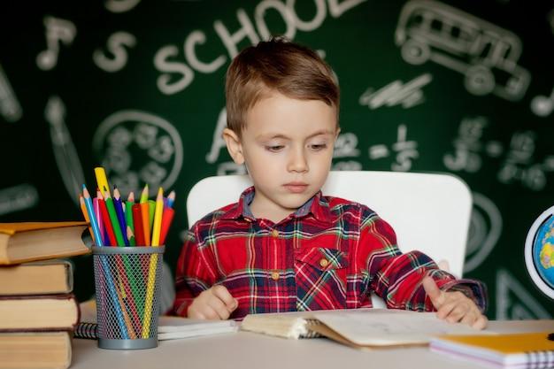 귀여운 영리한 소년 손에 돋보기와 책상에 앉아있다. 아이는 칠판으로 책을 읽고 있습니다. 학교 갈 준비. 학교로 돌아가다