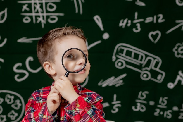 Cute clever boy is sitting at a desk with magnifying glass in hand. child is reading a book with a blackboard on a background. ready for school. back to school