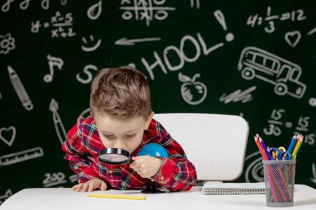 Cute clever boy is sitting at a desk with magnifying glass in hand. child is reading a book with a blackboard . ready for school. back to school