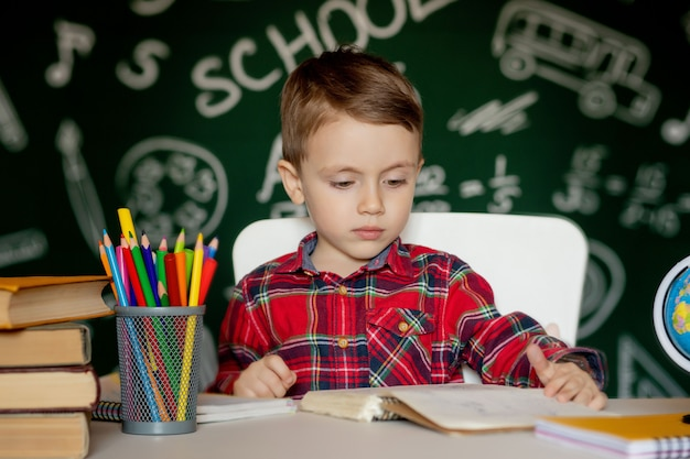 Cute clever boy is sitting at a desk with magnifying glass in hand. child is reading a book with a blackboard. ready for school. back to school