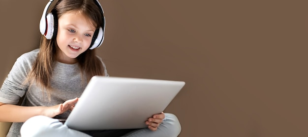 Cute clever little girl in wireless headphones using laptop at home