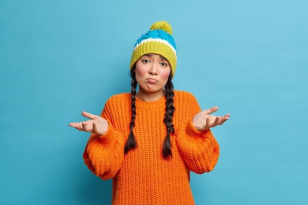 かわいい無知な女の子は肩をすくめ、正面を見ると疑わしいように見えます手のひらは疑わしい表情をしていますニット帽をかぶっていて、セーターは青い壁に隔離されているのを知らないか、助けられません