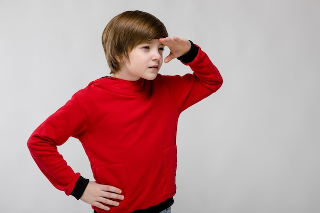 Cute confident curious little caucasian boy in red sweater looking for something on grey background