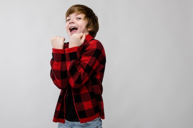 Cute confident excited smiling little caucasian boy in checkered shirt showing yes sign on grey