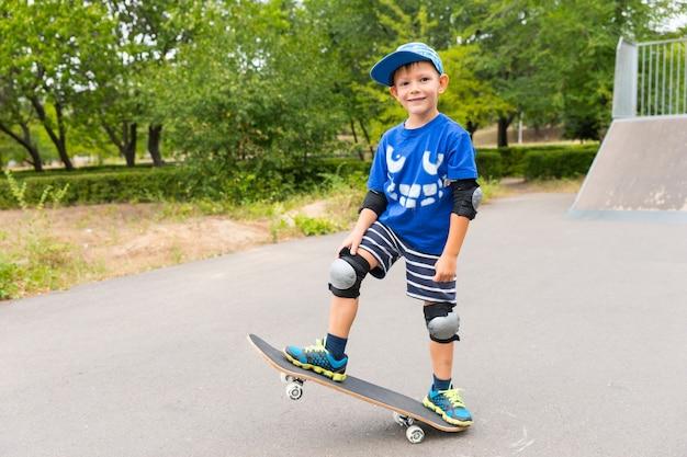 カメラに向かってニヤリと笑いながら、片方の端を空中に持ち上げてスケートパークのスケートボードでポーズをとっているかわいい自信のある小さな男の子