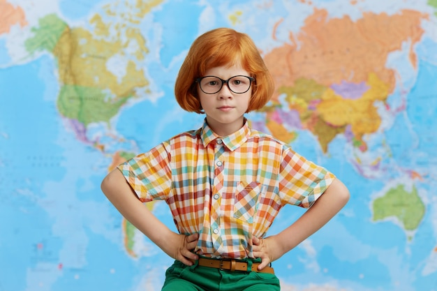 Cute confident little boy with ginger bob hairstyle wearing eyeglasses holding hands on his waist, posing against world map. childhood, learning and education