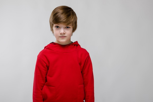 Cute confident little caucasian boy in red sweater on grey