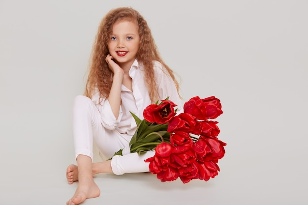 Cute confident little schoolgirl sitting on floor, looking smiling at front, keeping hand under chin, holding bouquet of red tulips