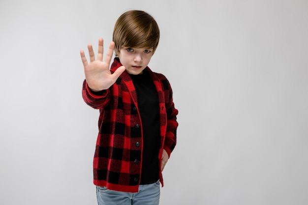 Cute confident sad little caucasian boy in checkered shirt showing stop sign on grey