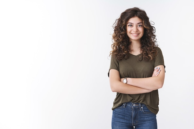 巻き毛のクロスアーム胸の自信を持って準備ができているかわいい自信を持って成功した若い女性のダイアトロジストは、広く幸運な日を感じ、白い背景に立って笑顔で役立つアドバイスを提供します