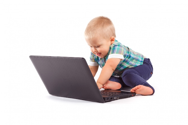Cute confused baby boy playing computer