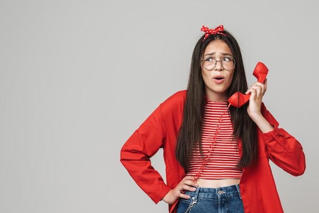 Милая смущенная девочка-подросток в повседневной одежде стоит изолированно над серой стеной и звонит на стационарный телефон