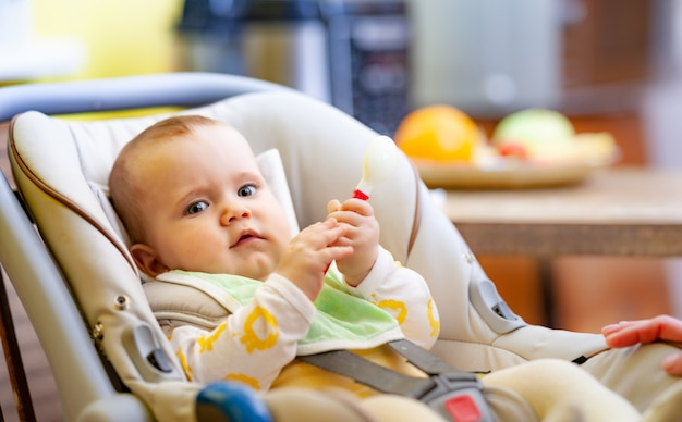 Cute contented little caucasian six-month-old girl sits in a child seat and plays with her beloved rattle.
