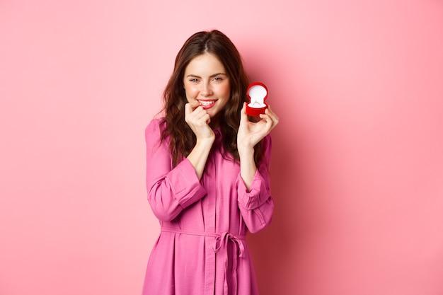 약혼 반지를 보여주는 동안 웃고, 손가락을 물고 킥킥 웃고, 결혼하고, 결혼 제안을 받고, 분홍색 벽에 서있는 귀여운 요염한 여자.
