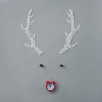 Cute countdown to christmas with reindeer face formed of snow antlers, cone eyes and a red alarm clock counting down to midnight for a nose over grey with copyspace